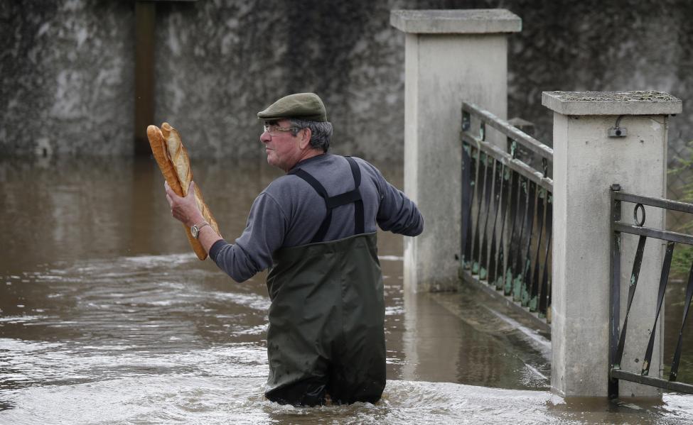 Một người đàn ông đang mang hai chiếc bánh mì baguettes truyền thống của Pháp về nhà. Ảnh: Christian Hartmann / Reuters