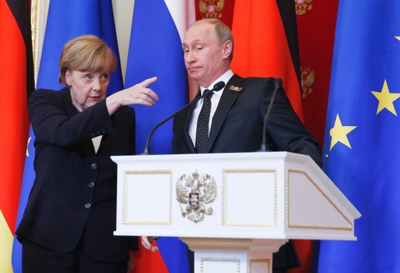 Bà Angela Merkel chỉ ông Vladimir Putin nhìn một điểm quan trọng trong một hội nghị sau đàm phán hòa bình tại Kremlin ngày 5/10/2015. Ảnh Reuters