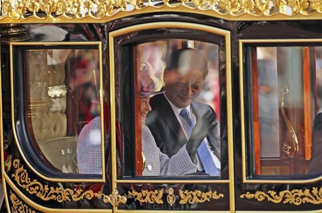 Nữ hoàng Elizabeth II và Chủ tịch Trung Quốc Tập Cận Bình ngồi trên xe ngựa hoàng gia đi trên đại lộ The Mall để tới cung điện Buckingham ở London ngày 20/10. Nhà lãnh đạo Trung Quốc và đệ nhất phu nhân Bành Lệ Viên đang có chuyến thăm cấp nhà nước tới Anh - Ảnh: Reuters.