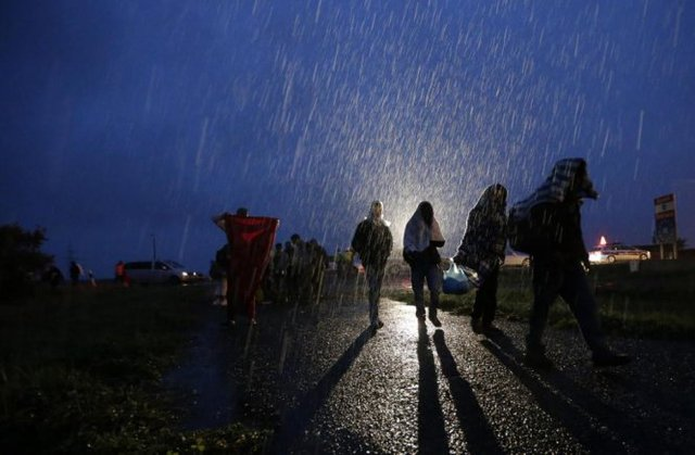 Những bóng người di cư đi lại dưới cơn mưa nặng hạt ở biên giới Áo - Hungary - Ảnh: AP
