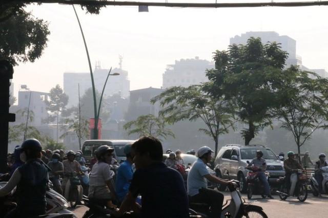 Người đi đường cần đeo khẩu trang vì màn mù có thể ảnh hưởng sức khỏe - Ảnh: Yến Trinh