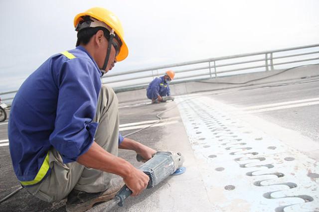 Công nhân đang chùi rửa, mài dũa mặt cầu trước giờ thông xe