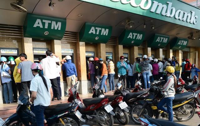 Nhiều công nhân hiện phải tăng ca mới đủ chi phí để trang trải mức sống tối thiểu. Trong ảnh: công nhân rút tiền tại KCX Tân Thuận, Q.7, TP.HCM - Ảnh: Thuận Thắng