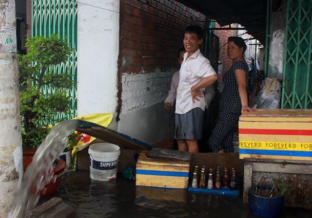 Một hộ dân ở đường Ấp Chiến Lược (Q.Bình Tân, TP.HCM) bơm nước từ trong nhà ra ngoài sau cơn mưa ngày 9-9 - Ảnh: ĐỨC PHÚ