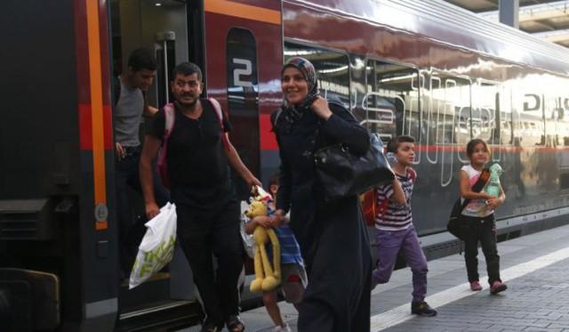 Người tị nạn tươi cười bước ra khỏi chuyến tàu hoả tại Áo - Ảnh: Reuters