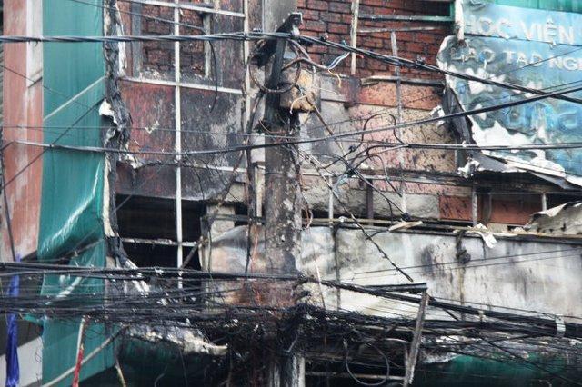 Trụ điện cạnh tòa nhà cháy đen xì khiến cả khu vực bị tắt điện. Ảnh: PHAN THÀNH