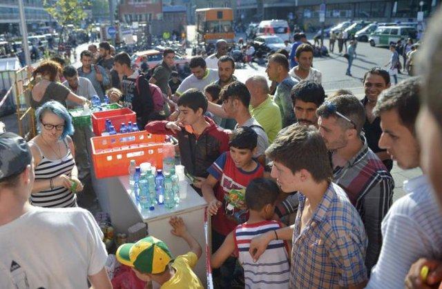 Người dân địa phương cung cấp nước uống miễn phí cho dân tị nạn - Ảnh: Reuters