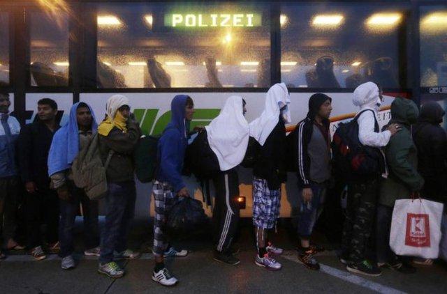 Hàng dài người dân tị nạn xếp hàng lên xe buýt để đi đến Áo - Ảnh: AP