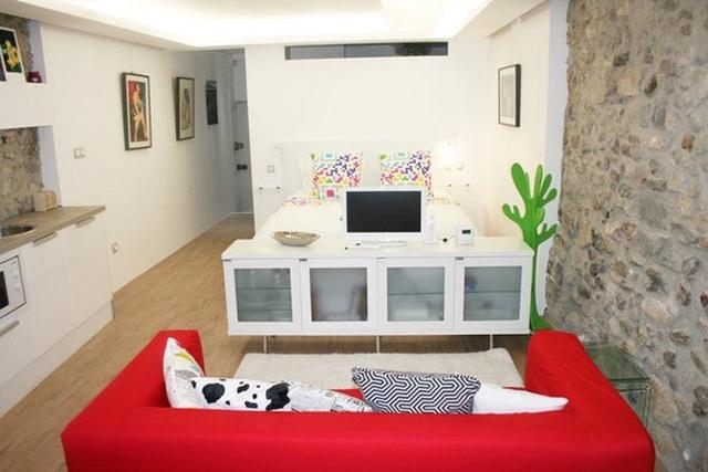 Còn ngôi nhà này được thiết kế với tông màu trắng của nội thất, màu nâu nhạt của tường đá giúp chiếc sofa đỏ nổi bật hơn.