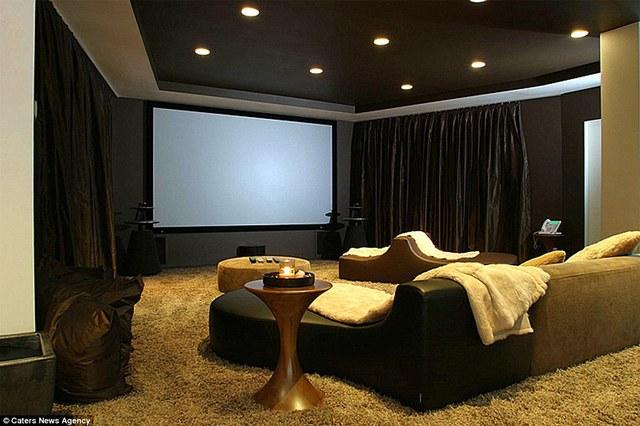 Phòng khách sang trọng có một màn hình lớn và những chiếc ghế cong độc đáo.