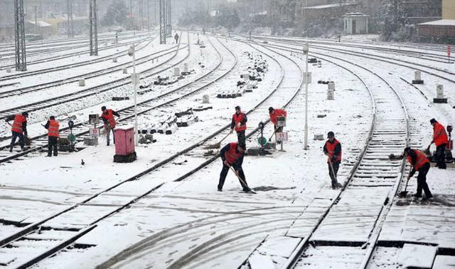 Công nhân dọn tuyết trên đường ray bên ngoài một nhà ga xe lửa ở Nam Xương, tỉnh Giang Tây - Ảnh: Reuters