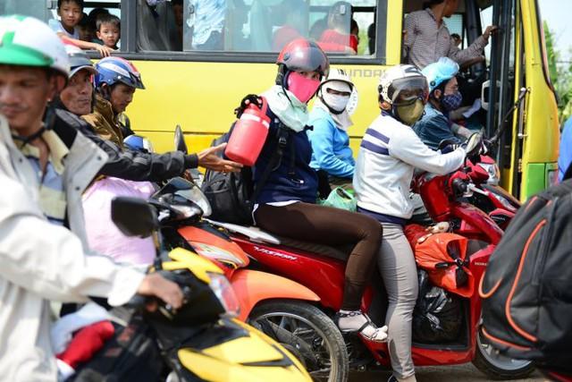 Người dân tranh thủ uống nước chờ đợi đường thông thoáng - Ảnh: Thanh Tùng
