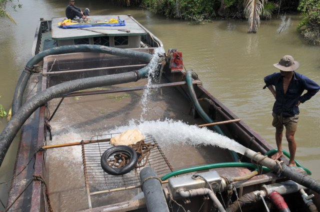 Người trồng sầu riêng ở xã Tam Bình (Cai Lậy) phải vào sâu trong rạch Rau Răm (xã Phú Phong, Châu Thành, Tiền Giang) bơm nước ngọt vào ghe bơm cát để mang về tưới cây - Ảnh: Mậu Trường