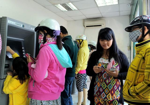 Chị Thúy Phương (thứ hai từ phải, quê An Giang), làm việc tại một công ty của Nhật Bản - đi rút tiền tại ATM, Q.7 TP.HCM sáng 10-1, cho biết năm nay được thưởng 1,5 tháng lương, nhiều hơn năm ngoái nên dịp tết năm nay cũng có dư chút đỉnh tiền mua sắm tết - Ảnh: Tự Trung