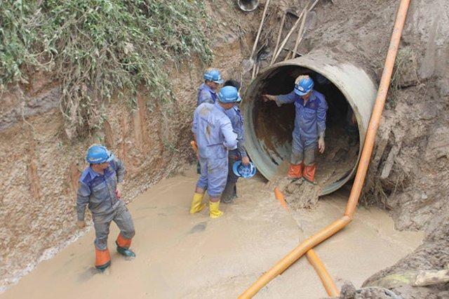 Công nhân khắc phục đoạn ống nước sông Đà bị vỡ lần thứ 13 - Ảnh: Tuấn Anh