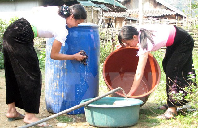 'Người dân Lai Châu lau rửa lu, vại chứa nước để diệt bọ gậy, phòng chống muỗi lây truyền dịch bệnh do virus Zika. (Ảnh: TTXVN/Vietnam+)'