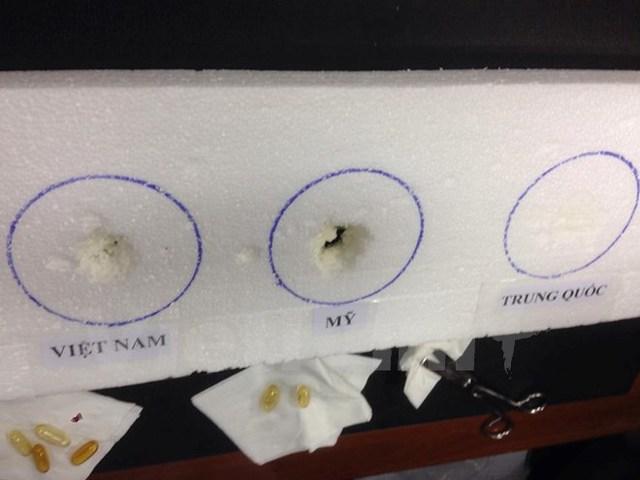 Thử nghiệm dầu cá ăn mòn xốp tại cuộc họp báo. (Ảnh: PV/Vietnam+)