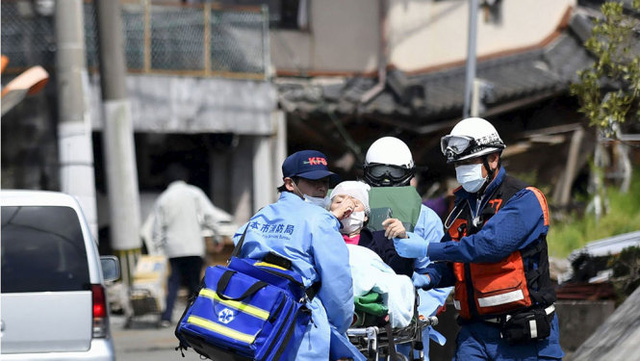 Một nạn nhân cao tuổi được nhân viên cứu hộ đưa ra khỏi nơi nguy hiểm - Ảnh: Reuters