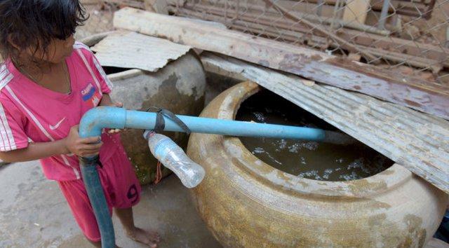 Một bé gái ở Kandal, Campuchia đang chờ bơm nước vào lu chứa - Ảnh: AFP