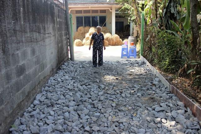 Mẹ Nguyễn Thị Em đang đừng nhìn con đường vào nhà mình.