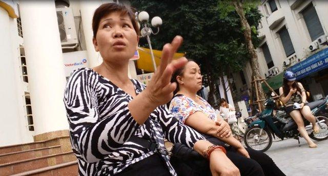 Môt người mua đi bán lại tiền lưu niệm ngồi trước phố Đinh Lễ để mời khách - Ảnh: Quang Thế