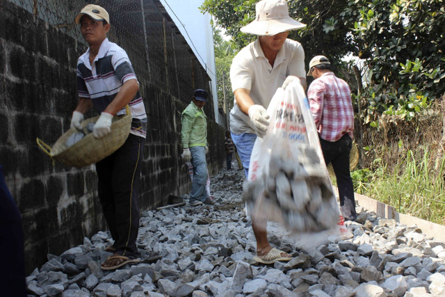 Công nhân đang nhặt đá rải đều con đường để đổ bê tông. Dự kiến con đường vào nhà mẹ Em sẽ hoàn thành trong vòng 1 tuần.