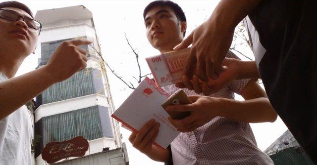 Tốp thanh niên rao bán tiền trước cửa ngân hàng - Ảnh: Quang Thế