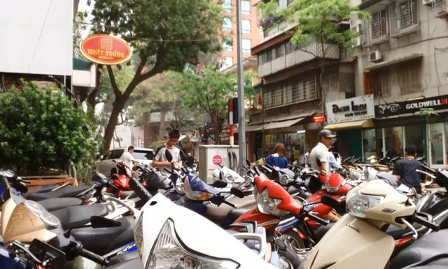 Một bãi xe tự phát mọc lên trước sảnh Ngân hàng Nhà nước thu với giá 10.000 đồng/lần gửi - Ảnh: Quang Thế