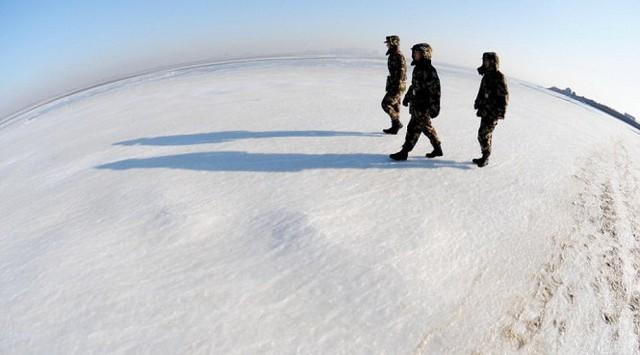 Binh sĩ Trung Quốc đi trên mặt biển đóng băng ở thành phố Thanh Đảo, tỉnh Sơn Đông - Ảnh: REX
