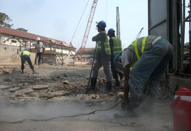 Công nhân dùng máy khoan thay nhau đẩy đất còn dính lại từ các trụ sắt tạm dùng để đỡ sàn.