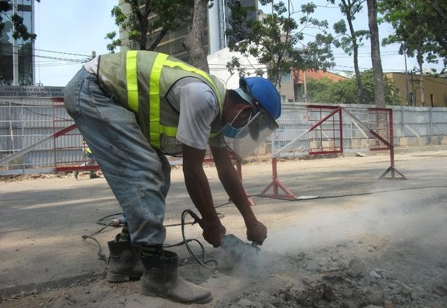 Một công nhân vẫn đang miệt mài cắt bê tông dưới cái nắng chói chang.