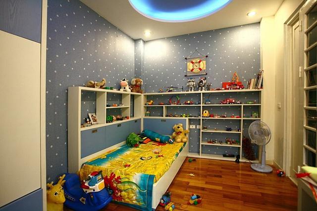 Trong phòng của trẻ có cột lồi ra ở góc phòng, nhà thiết kế đã dùng hai chiếc kệ bằng đúng phần lồi ra để trả lại sự vuông vắn cho không gian.