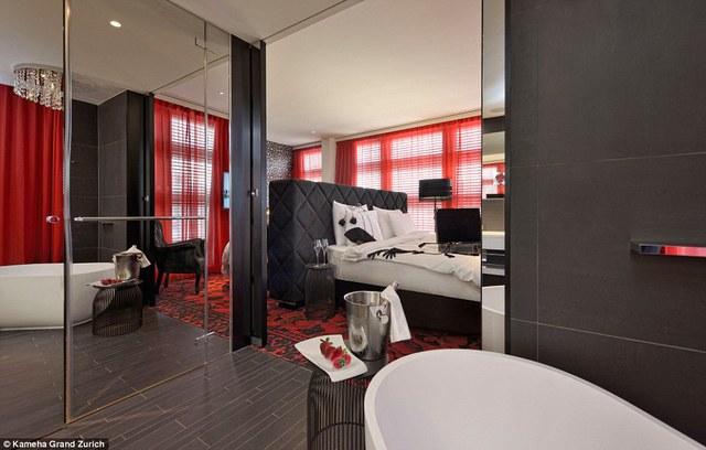 Một chiếc giường ngủ lớn màu trắng nổi bật giữa hai màu đen đỏ.