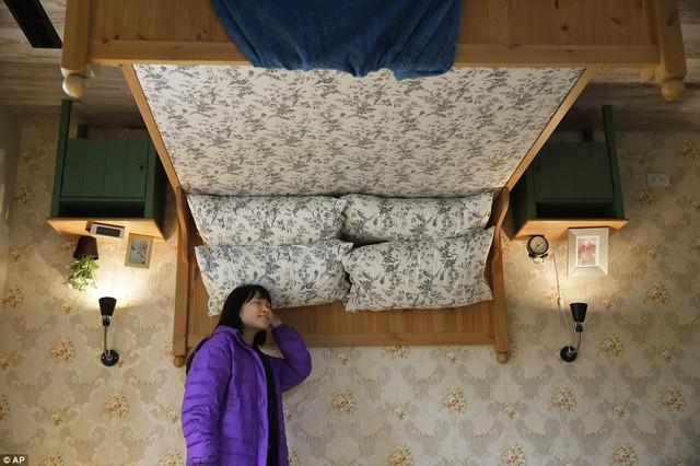 Một khách du lịch thích thủ với chiếc giường ngủ lộn ngược.