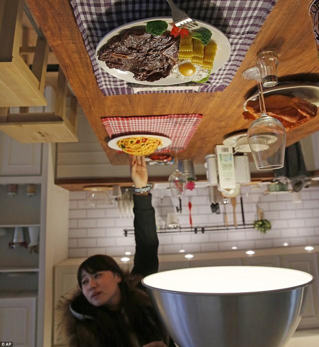 Một khách du lịch thích thú với một đĩa mì spaghetti nhựa đã được gắn chặt vào một bảng trên trần phòng bếp.