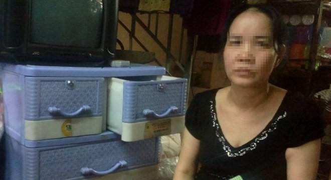 Ảnh: Bà Nguyễn Thị Loan thẫn thờ bên cuốn sổ cho vay giờ đã trở thành giấy lộn