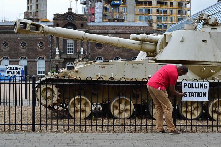 Một nhân viên bỏ phiếu dán tấm biển địa điểm bỏ phiếu bên ngoài hàng rào bảo tàng lịch sử Greenwich Heritage Centre. Ảnh: Getty Images