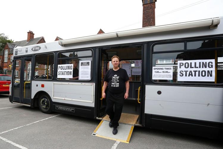 Người dân rời địa điểm bỏ phiếu tạm thời được đặt trên một chiếc xe buýt. Ảnh: Getty Images