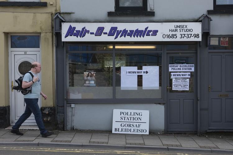 Một cử tri đi ngang qua địa điểm bỏ phiếu được đặt trong một cửa hàng cắt tóc ở Merthyr, Wales. Ảnh: Getty Images.