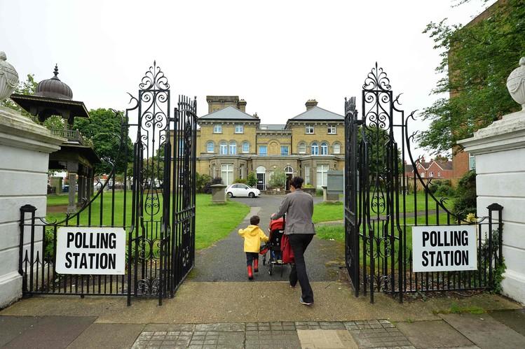 Một người mẹ đưa hai con đến địa điểm bỏ phiếu tại bảo tàng Hove. Ảnh: Getty Images