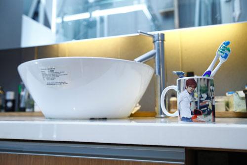 Phòng tắm rộng rãi với cốc nước in hình ảnh của chủ nhân căn hộ.