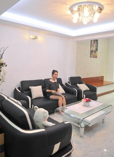 Phòng khách nổi bật với hai gam màu trắng đen. Phòng này được chia làm 2 khu vực là bàn salon để tiếp khách và khu vực treo nhiều ảnh lưu niệm của gia đình.