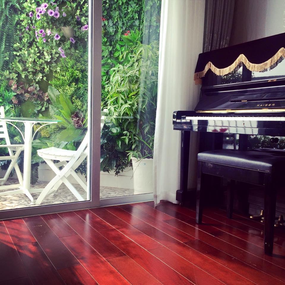 Góc đặt piano cạnh ban công đầy nắng, gió và hoa cỏ trong căn hộ.