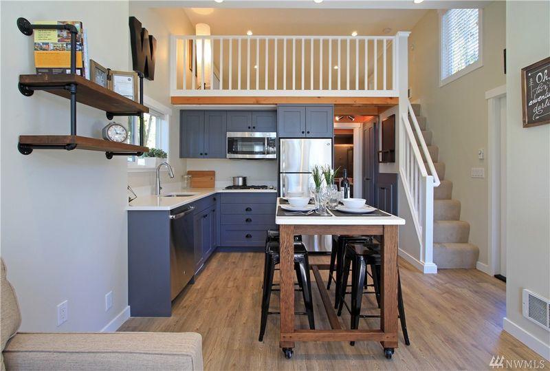 Căn nhà còn có một gác lửng với lối lên bằng cầu thang gỗ sơn màu trắng.