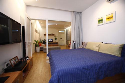 Phòng ngủ ngăn cách với phòng khách bằng một tấm kính lớn tạo cảm giác không gian không bị giới hạn. Những lúc muốn nghỉ ngơi riêng tư chỉ cần kéo tấm rèm lại.