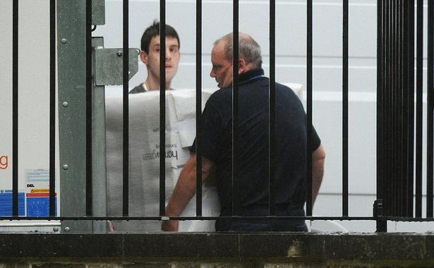 Công nhân khiêng đồ ra khỏi tòa nhà - Ảnh: DailyMail