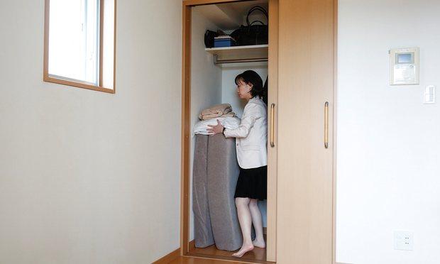 Chị Saeko đang cất toàn bộ đệm và chăn vào tủ.