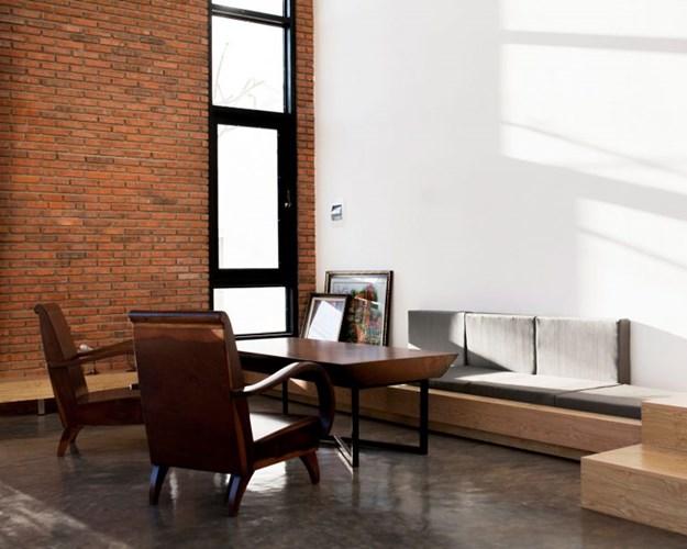 Một phần tường nhà bằng gạch mộc tạo điểm nhấn độc đáo cho không gian phòng khách.