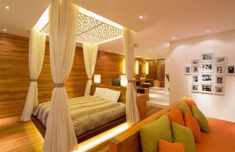 Không gian phòng ngủ rộng thoáng và ấm áp với chất gỗ, vải, màn và đèn trang trí.