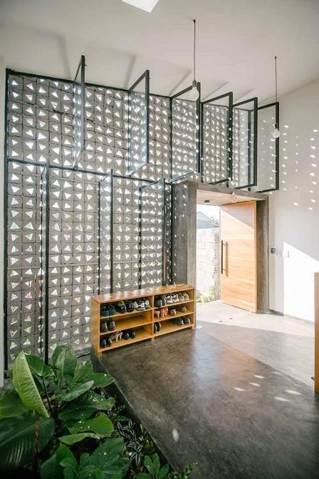 Tường của ngôi nhà được xây bằng gạch với các ô thoáng giúp cho ánh sáng và gió vào được bên trong. Để khắc phục vấn đề bụi bặm hay những khi trời mưa, gia chủ bố trí một hệ cửa kính với dây nối giúp đóng mở một cách dễ dàng.